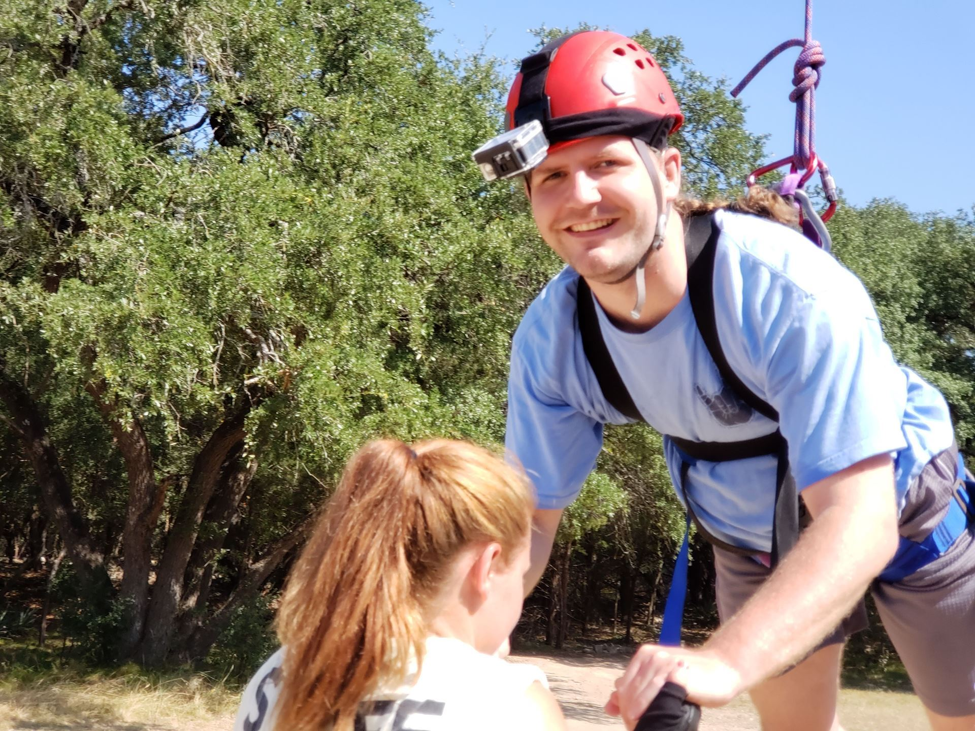 Patrick Vellia hangs, smiling, near trees in a belay harness and red helmet, after jumping off a 40-ft telephone pole platform. Camp Staff guide him to open ground to demonstrate the experience in PT to the next brave soul.