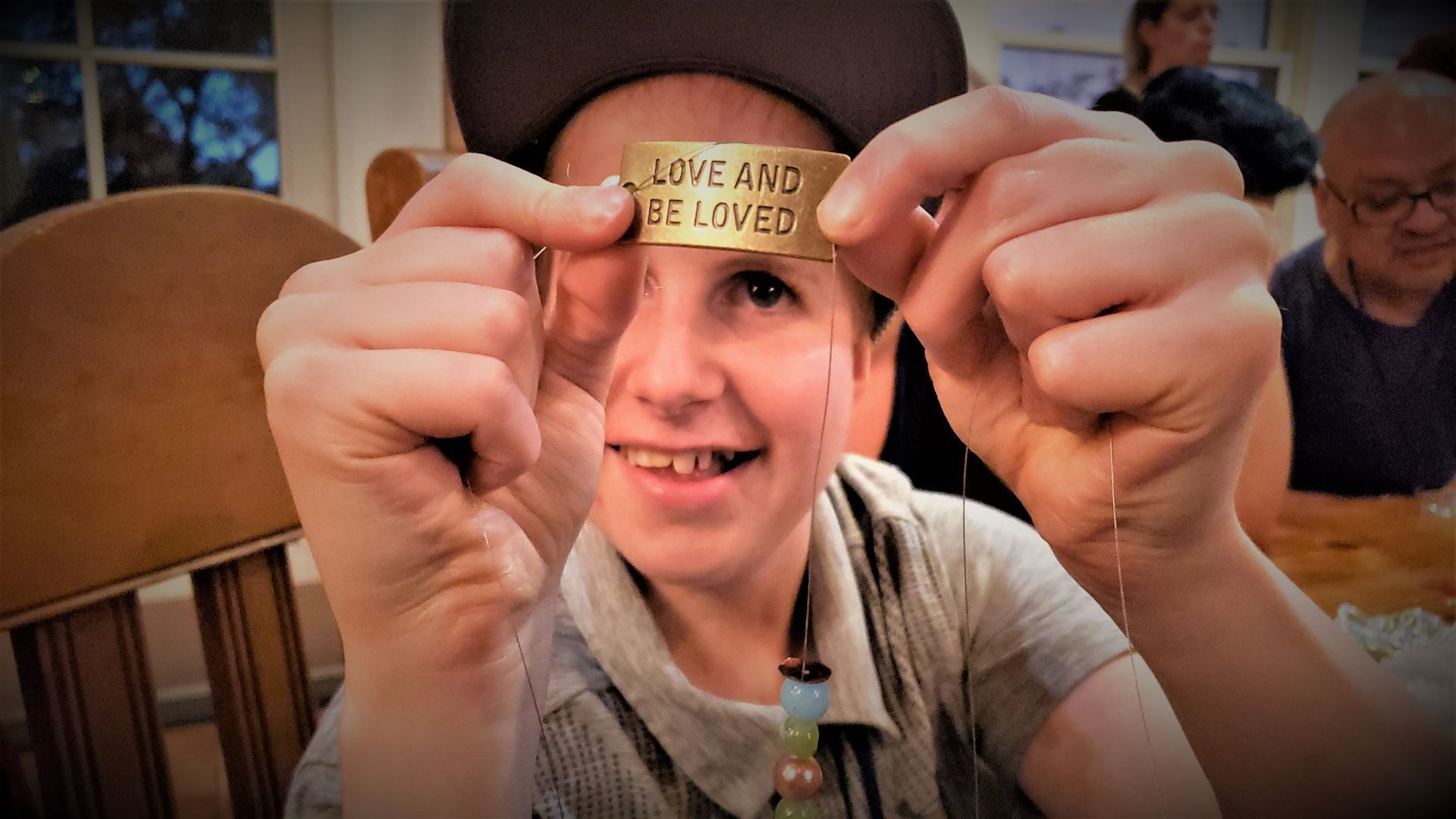 During a beading activity, a smiling Jr holds a gold metal plate with the words,