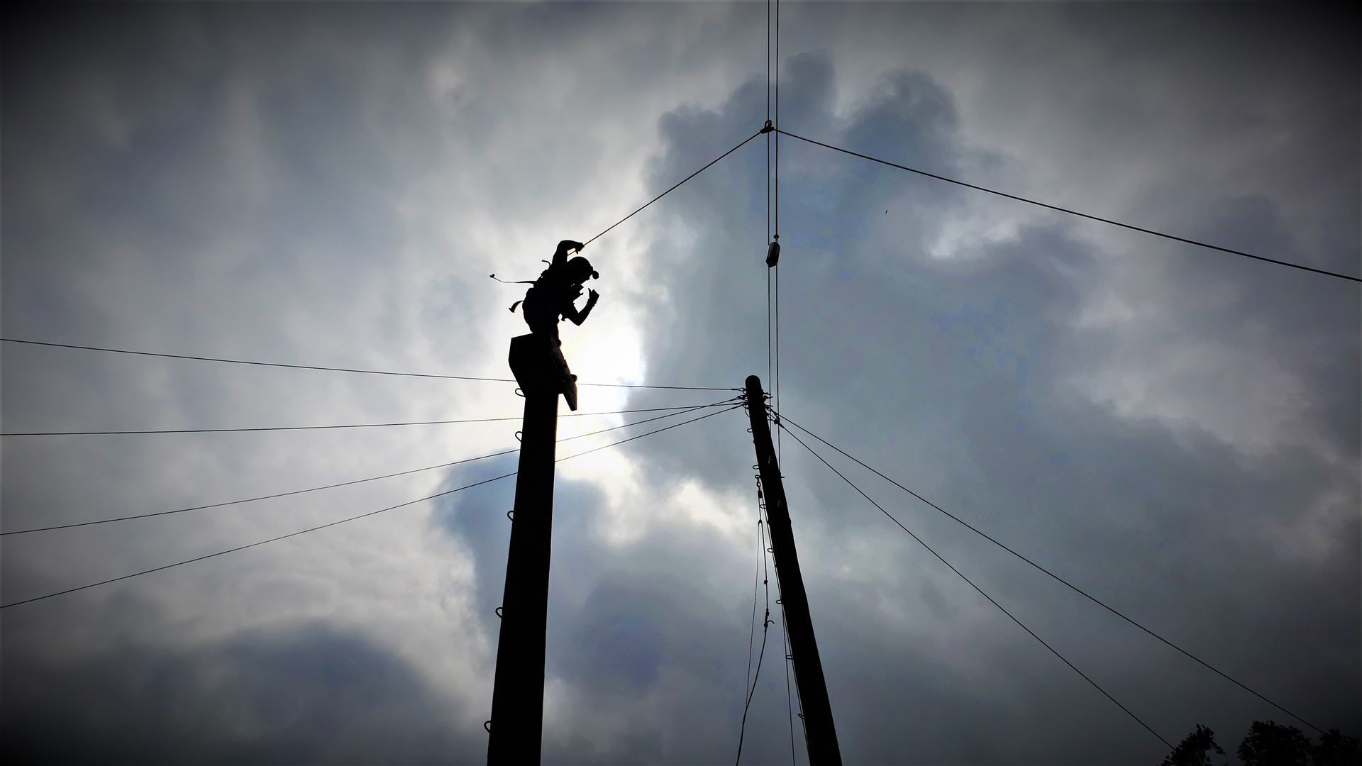 Silhouetted by the sun, a Jr strikes a powerful pose atop a 40-ft pole, ready for the challenge to punch a hanging buoy, a 5-ft jump away.