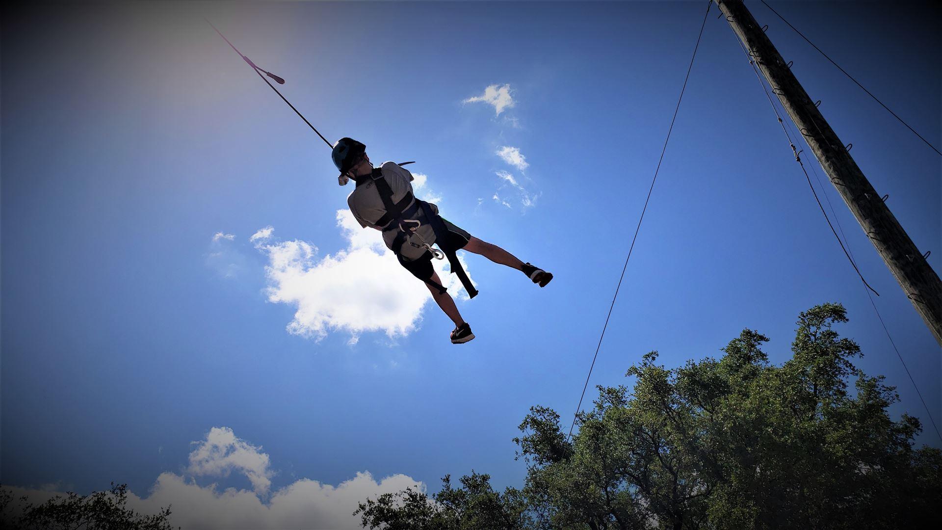A Jr swings across wispy clouds in a blue sky above the trees.