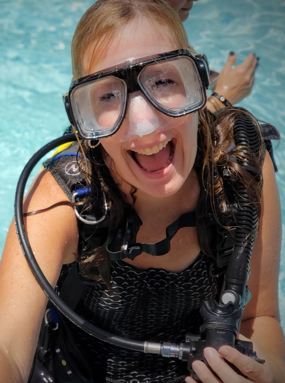 Mindy Dill laughs coming up from the water in full scuba gear.